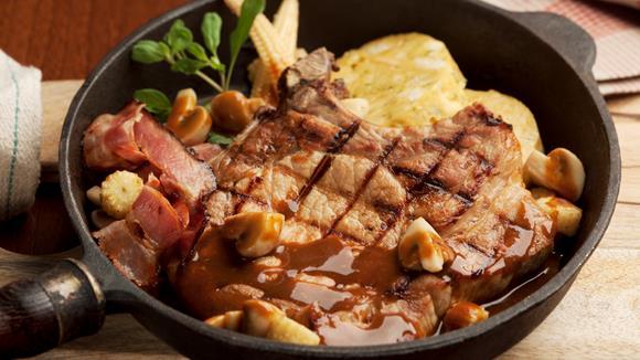 Schweinskoteletts in Biersauce mit Champignons, Bacon und Serviettenknödeln