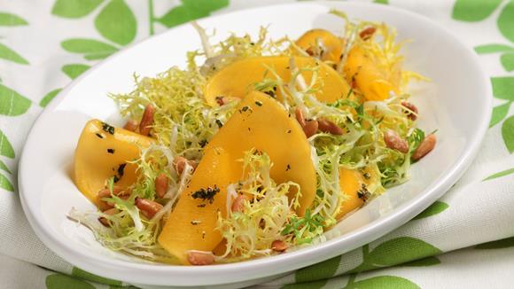 Friséesalat mit Mangos und Pinienkernen
