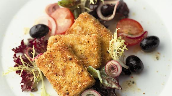 Gebackener Schafskäse in Croûtons paniert auf Salat mit Oliven und Tomaten Rezept