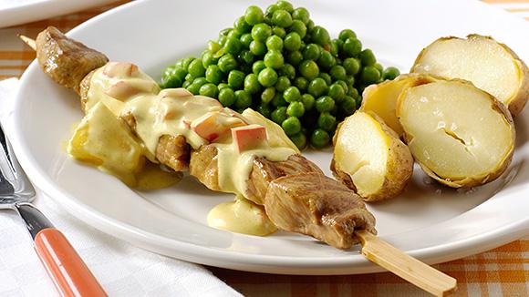 Vleessatés en currysaus, paprika, ananas, doperwtjes en gepofte aardappel