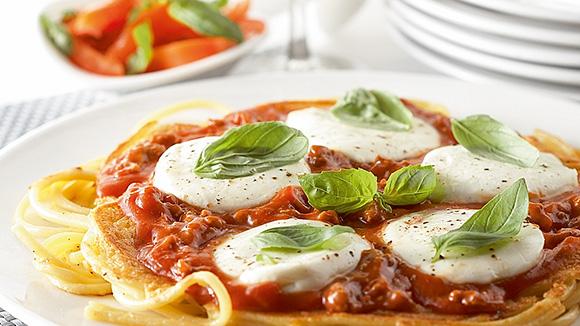 Pasta pizza met gehakt, mozzarella en basilicum