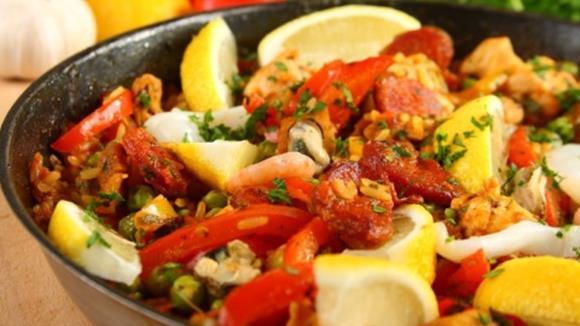 Paella a la navarro mit Huhn, Paprika, Fisolen und Zitronenspalten