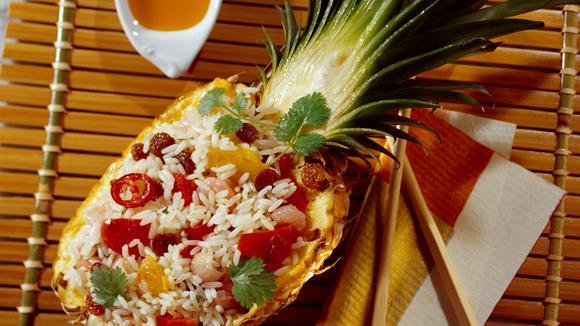 Gebratener Reis mit Peperoni, Shrimps und Korinthen in Ananas